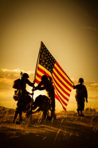 American Soldiers dressed in authentic WWII uniforms stand on a hill in the desert. They are placing the American flag into the ground. Four of the soldiers are assisting each other in standing the flag while the fifth soldier holds the flag up. There is a golden sunset behind them making the men silhouettes.