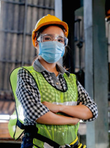 Factory woman worker or technician with hygienic mask stand with confident action with her co-worker as background. (Factory woman worker or technician with hygienic mask stand with confident action with her co-worker as background., ASCII, 117 comp