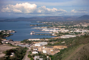 High oblique view of Naval Station Guantanamo Bay, Cuba looking northeast. Corinaso Point is on the left. A USCB cutter is moored at Pier D, an LST is moored at Pier L and a Spruance Class destroyer is moored at Pier V.
